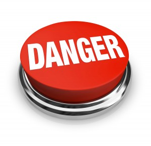 A red button with the word Danger, illustrating the hazards and